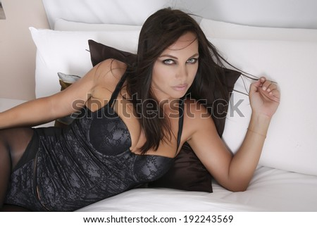 Beautiful, sexy and Attractive Sexy Pinup Female Model in black body elongated on a bed - stock photo
