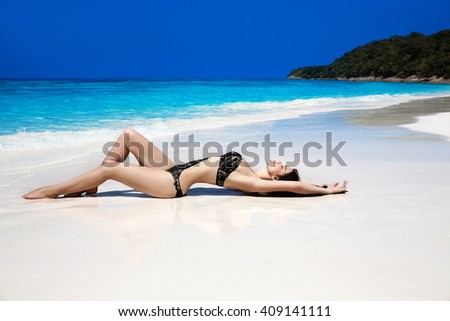 Beautiful sexy bikini model woman lying on exotic tropical beach beside blue water by seashore. Summer vacation. Sun tanning girl on white sand. - stock photo