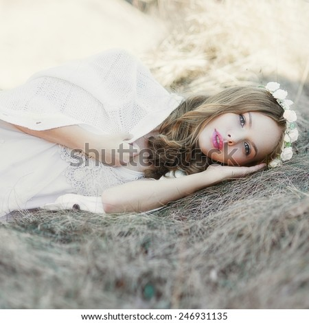beautiful sexy blond girl lying in a field in spring - stock photo
