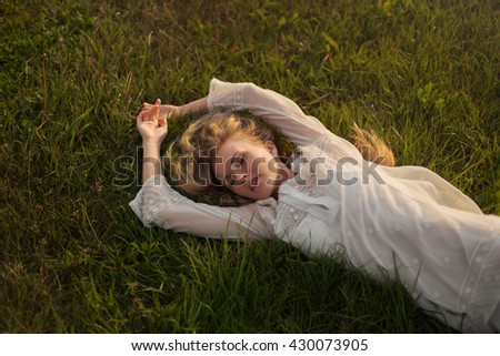 beautiful sexy blond girl lying on the grass