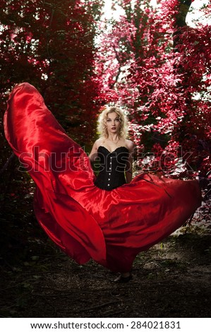 Beautiful sexy blonde girl in a black corset and red skirt with a long train posing in amongst the trees and foliage - stock photo