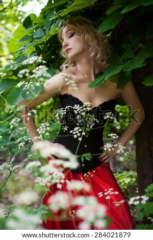 Beautiful sexy blonde girl in a black corset and red skirt with a long train posing in green leaves at the tree