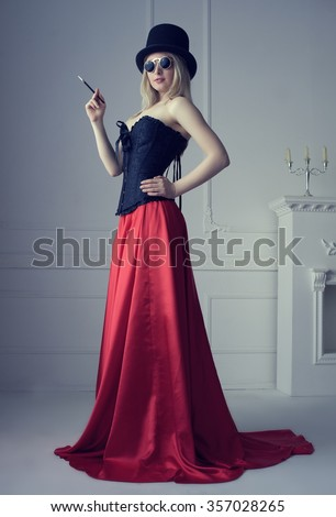 Beautiful sexy blonde girl in a corset long red skirt and a black hat with a cylinder mouthpiece posing against a white wall - stock photo