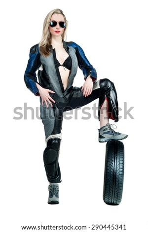 Beautiful sexy blonde girl in a motorcycle suit posing on a white background with wheels isolated - stock photo