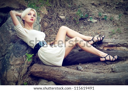 Beautiful sexy blonde girl posing on the felled trees - stock photo