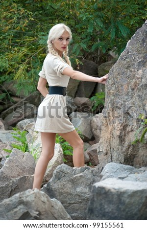 Beautiful sexy blonde girl posing on the rocks
