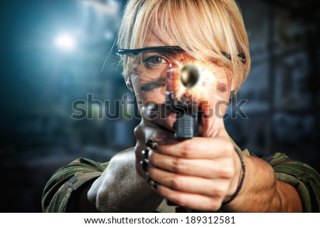 Beautiful sexy blonde girl with gun shooting - stock photo