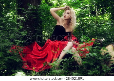 Beautiful sexy blonde in a black corset and red skirt with a long train posing sitting in green foliage - stock photo