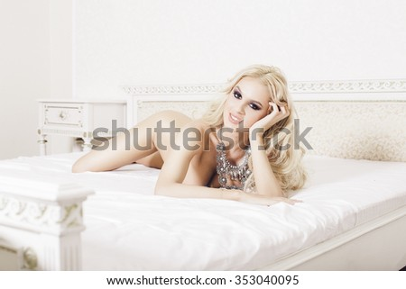 Beautiful sexy blonde posing naked in bed - stock photo
