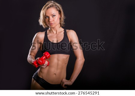 Beautiful sexy blonde with dumbbells on a black background.