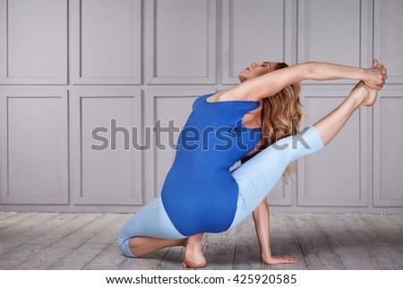 Beautiful sexy blonde with perfect athletic slim figure engaged in yoga, exercise or fitness, lead a healthy lifestyle, and eats right, dressed in comfortable casual clothes relaxes and meditation - stock photo