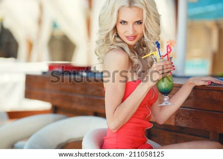 beautiful sexy blonde Woman in bar on Hawaii at beach club at sunset. Beautiful girl enjoying alcoholic beverage cocktail outside. Smiling happy Caucasian blonde woman on Hawaiian beach. - stock photo