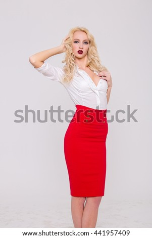 beautiful sexy blonde woman in fashionable business clothing. beautiful glamorous girl in white blouse and red skirt