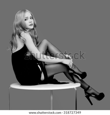 Beautiful sexy blonde woman in stockings and heels sitting on table, black and white photo - stock photo