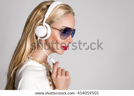 Beautiful sexy blonde woman with long hair and perfect body in an elegant white suit sitting with headphones on and listen to music and sensual looks, has red lips and seductive eyes