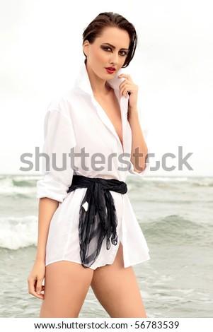 Beautiful sexy brunette bikini model on the beach at sunset - stock photo