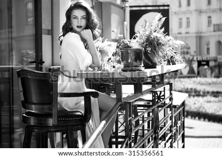 Beautiful sexy brunette girl dark hair evening makeup red lipstick long silk dress perfect shape tanned body, accessories jewelry watches handbag walking down the street, sitting into the cafe waiting - stock photo