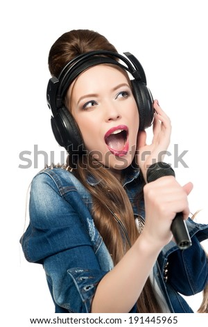 Beautiful sexy brunette girl in jeans suit posing on a white background with a microphone and headphones isolated