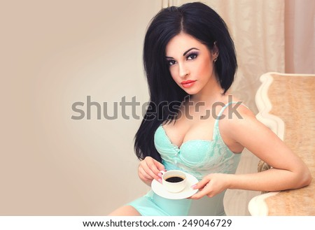 Beautiful sexy brunette girl in lingerie drinking coffee on a beige background space board - stock photo