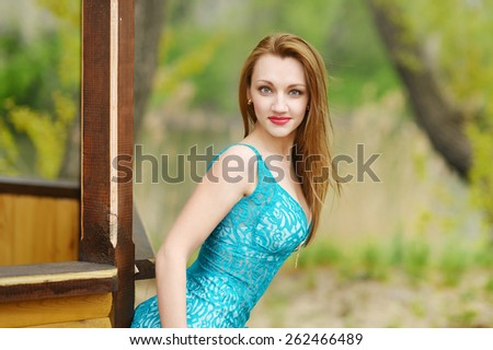 beautiful sexy brunette girl in short blue dress, high heels, with big Breasts and long legs on the street in the Park near the wooden gazebo. Girl walks near the lake - stock photo