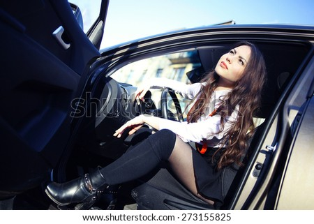 beautiful sexy brunette in a car - stock photo