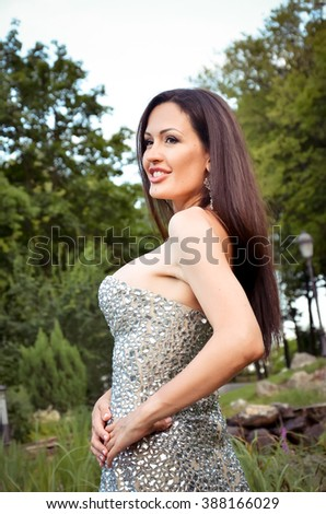 beautiful sexy brunette in a luxurious dress in the park