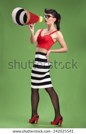 Beautiful sexy brunette pin up girl in striped dress with vintage megaphone - stock photo