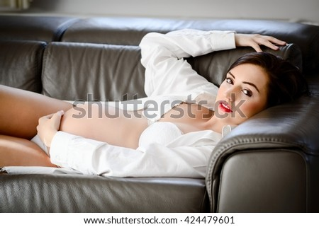 Beautiful sexy brunette pregnant woman in white shirt and lingerie lying on the sofa  - stock photo