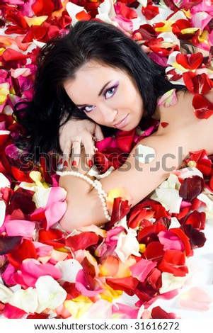 Beautiful sexy brunette woman in colorful rose petals - stock photo