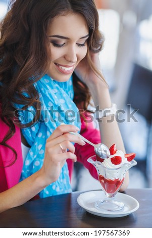 Beautiful sexy brunette woman in restaurant cafe with ice cream cake alluring woman in bright clothes and hairstyle and makeup eating dessert. Beauty fashion  - stock photo
