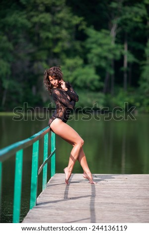 Beautiful sexy brunette woman wearing black panties and body-stocking posing by the lake - stock photo