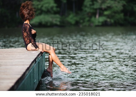 Beautiful sexy brunette woman wearing black panties and body-stocking sitting by lake playing with hair - stock photo
