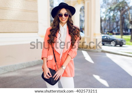 Beautiful  sexy brunette young lady with perfect slim body, long legs ,  bright make up, amazing wavy hairstyle. Model walking on summer day  on the street. White high heels. Casual style.