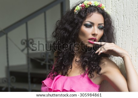 Beautiful sexy brunette young woman with wreath of colorful flowers in curly hair and bright makeup in pink clothes standing near white wall and stairs looking away, horizontal picture - stock photo