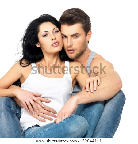 Beautiful sexy couple in love on white background dressed in blue jeans and white undershirt - stock photo