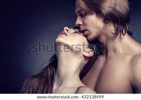 Beautiful sexy couple on a dark background - stock photo