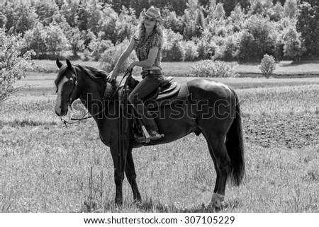 Beautiful sexy cowgirl sitting on a horse. - stock photo