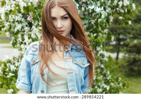 beautiful sexy cute sweet girl with long red hair and green eyes in a denim jacket near a flowering tree in the park the wind blowing her hair