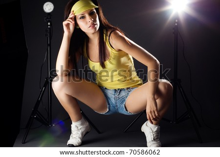 Beautiful sexy dancer with flash light in background. - stock photo