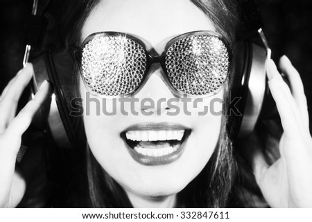 beautiful sexy disco woman, smiling and listening to music with sparkle covered sunglasses. Perfect for stylish club, disco and fashion events  - stock photo