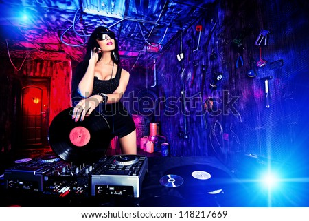 Beautiful sexy DJ girl working on a party in the old garage. - stock photo