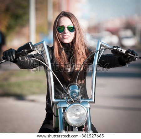 Beautiful sexy elegance haired hair woman driver, has happy fun cheerful smiling face, black leather jacket, sunglasses. Has slim sport body. Motion on great motorcycle urban city. Portrait street.  - stock photo