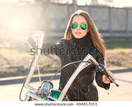 Beautiful sexy elegance haired hair woman driver, has happy fun cheerful smiling face, black leather jacket, sunglasses. Has slim sport body. Motion on great motorcycle urban city. Portrait street - stock photo