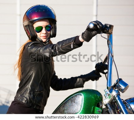 Beautiful sexy elegance haired hair woman driver, has happy fun cheerful smiling face, black leather jacket, sunglasses. Has slim sport body. Motion on great motorcycle urban city. Portrait street.