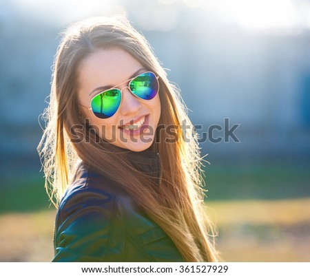 Beautiful sexy elegance haired hair woman, has happy smile face, black leather jacket, sunglasses. Has slim sport body. Portrait in the street urban city.  - stock photo