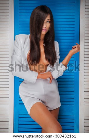 Beautiful sexy elegant brunette lady with long healthy hair posing, looking at camera. Sensual woman with naked breast. Studio shot. - stock photo