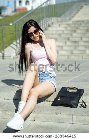 Beautiful sexy fashion girl sitting on stairs and talking on the phone lying next bag, relaxed contentedly resting