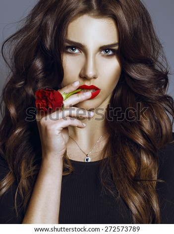 Beautiful Sexy fashion Woman smokes a rose.  Makeup with Red Lips, long perfect hair and Red rose. Beauty italian Girl. Passion. Makeup, Hairdo and sexy figure. Concept of a Little black dress.  - stock photo