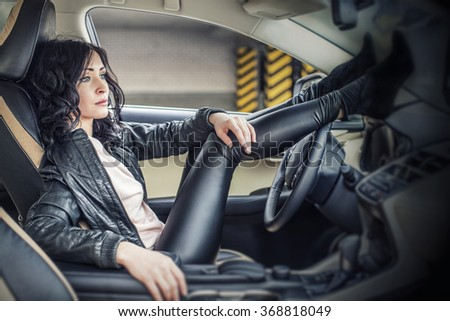 Beautiful sexy female model in leather clothes with a white car in the Parking lot - stock photo