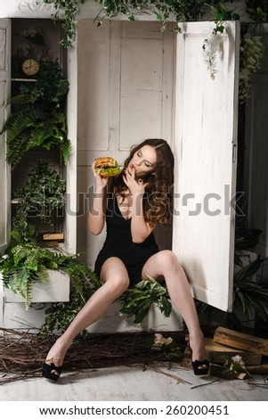 beautiful, sexy girl eating a burger. Concept. weight loss. - stock photo